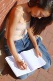Escritura de la muchacha en cuaderno Imagen de archivo
