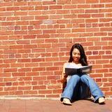 Escritura de la muchacha en cuaderno Imagen de archivo libre de regalías