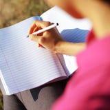 Escritura de la muchacha en cuaderno Fotos de archivo
