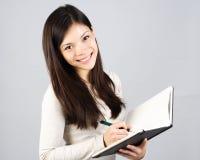 Escritura de la muchacha en cuaderno Fotografía de archivo