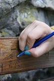 Escritura de la muchacha en el banco de madera Foto de archivo libre de regalías
