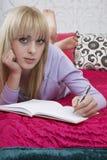 Escritura de la muchacha en el libro en cama Fotografía de archivo