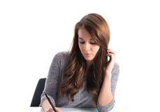 Escritura de la muchacha en el papel Fotografía de archivo libre de regalías