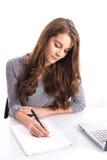 Escritura de la muchacha en el papel Foto de archivo