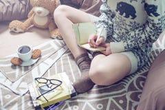 Escritura de la muchacha en un cuaderno que se sienta en la cama Foto de archivo