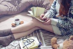 Escritura de la muchacha en un cuaderno que se sienta en la cama Imagen de archivo