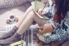 Escritura de la muchacha en un cuaderno que se sienta en la cama Fotografía de archivo libre de regalías