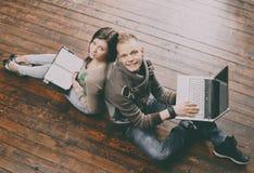 Escritura de la muchacha en un cuaderno y un muchacho con un ordenador portátil Imágenes de archivo libres de regalías
