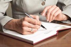 Escritura de la mujer de negocios con la pluma en libreta Fotos de archivo libres de regalías