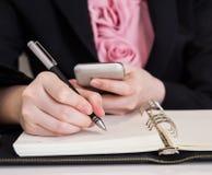 Escritura de la mujer de negocios en el cuaderno Fotografía de archivo libre de regalías