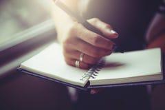Escritura de la mujer en el cuaderno en blanco en cama por la mañana fotografía de archivo libre de regalías