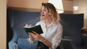 Escritura de la mujer en el planificador diario metrajes
