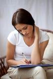 Escritura de la mujer en la libreta para hacer la lista en el país Fotos de archivo libres de regalías