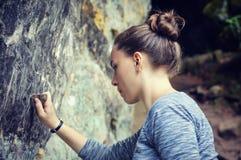 Escritura de la mujer en roca con la piedra Foto de archivo