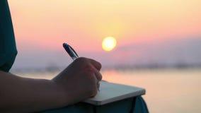 Escritura de la mujer en su diario en la puesta del sol almacen de video