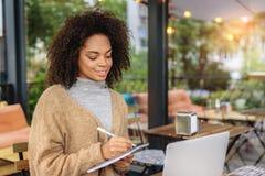 Escritura de la mujer en un cuaderno mientras que se sienta Fotos de archivo libres de regalías