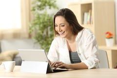 Escritura de la mujer en una PC de la tableta en casa Fotos de archivo libres de regalías