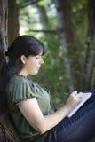 Escritura de la mujer joven en diario imagenes de archivo