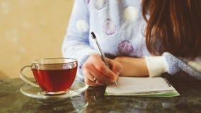 Escritura de la mujer joven en diario y té de consumición almacen de metraje de vídeo