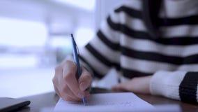Escritura de la mujer joven en el texto del cuaderno, pensando y soñando sobre algo bueno almacen de video