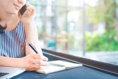 Escritura de la mujer de negocios en la libreta con una pluma y el hablar en Fotografía de archivo