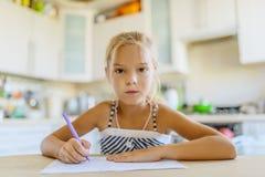 Escritura de la niña con la pluma en cuaderno Imagen de archivo