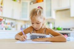 Escritura de la niña con la pluma en cuaderno Fotografía de archivo