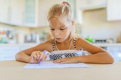 Escritura de la niña con la pluma en cuaderno Imagenes de archivo
