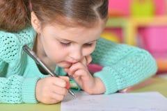 Escritura de la niña mientras que se sienta en la tabla Imagen de archivo