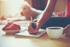 Escritura de la pluma en el cuaderno con café Foto de archivo