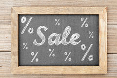 Escritura de la tiza de la venta con las muestras de porcentaje en la pizarra Imagen de archivo