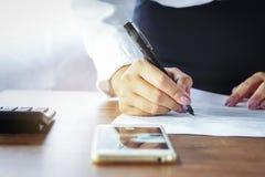 Escritura de la trabajadora en el papel en la oficina con el teléfono móvil Imagen de archivo libre de regalías