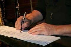 Escritura de notas musicales Foto de archivo libre de regalías