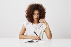 Escritura de pensamiento de la muchacha africana en el cuaderno que se sienta en la tabla sobre el fondo blanco Copie el espacio Fotografía de archivo