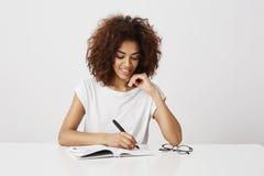Escritura de pensamiento de la muchacha africana en el cuaderno que sonríe sobre el fondo blanco Copie el espacio Foto de archivo