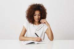 Escritura de pensamiento de la muchacha africana en el cuaderno que sonríe sobre el fondo blanco Copie el espacio Imágenes de archivo libres de regalías