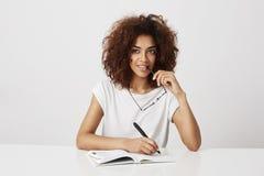 Escritura de pensamiento de la muchacha africana en el cuaderno que sonríe sobre el fondo blanco Copie el espacio Imagen de archivo libre de regalías