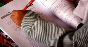 Escritura de Schooldchild en árabe imagen de archivo libre de regalías