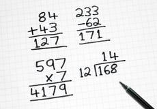 Escritura de sumas simples de la matemáticas en el papel cuadrado. Fotos de archivo