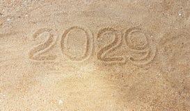 Escritura del año en la arena con alcance fuera de la mano del superviviente Fotos de archivo