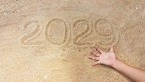 Escritura del año en la arena con alcance fuera de la mano del superviviente Foto de archivo libre de regalías