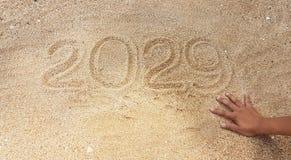 Escritura del año en la arena con alcance fuera de la mano del superviviente Fotos de archivo libres de regalías