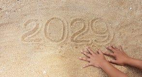 Escritura del año en la arena con alcance fuera de la mano del superviviente Fotografía de archivo libre de regalías