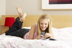 Escritura del adolescente en diario en dormitorio Fotos de archivo