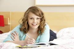 Escritura del adolescente en diario en dormitorio Imágenes de archivo libres de regalías