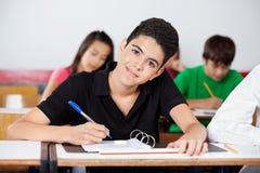 Escritura del adolescente en la sala de clase Imagen de archivo libre de regalías