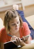 Escritura del adolescente en libro Foto de archivo libre de regalías