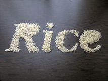Escritura del arroz de la palabra con las semillas del arroz en una tabla con el fondo de madera marr?n imagen de archivo