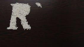 Escritura del arroz de la palabra con las semillas del arroz usando el movimiento y la animaci?n de parada