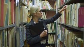 Escritura del bibliotecario de la mujer en el tablero en la biblioteca metrajes